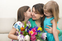 Happy woman and her little daughters in the living room Royalty Free Stock Photos