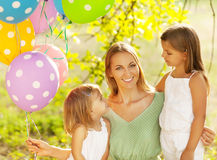 Happy woman and her little daughters in the park with ballons Stock Photos
