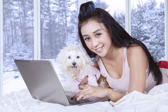 Happy woman and her puppy using laptop on bed. Young asian woman smiling at the camera while lying on the bed with her puppy and using laptop computer Stock Image
