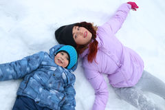 Happy woman and her son lie on white snow at winter day Stock Images