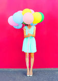 Happy woman is hides her head an air colorful balloons having fun over a pink background Stock Photography