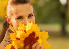 Happy woman hiding behind bunch of fallen leaves Royalty Free Stock Images