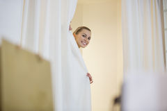 Happy woman in hiding behind curtains in store Stock Photo