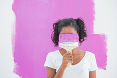 Happy woman hiding her face with paintbrush Stock Photo
