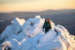 Happy Woman hiker with backpack standing on the mountain peak abd smiling at cold winter day. Female hero and active Royalty Free Stock Image
