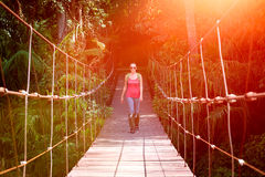 Happy woman hiker crossing suspension bridge in sunlight. Stock Photos