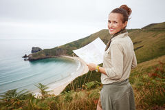 Happy woman hiker with map in front of ocean view landscape Stock Image