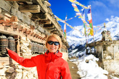 Happy woman hiker and prayer wheel in Nepal Royalty Free Stock Photo