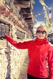 Happy woman hiker and prayer wheel in Nepal Stock Photos
