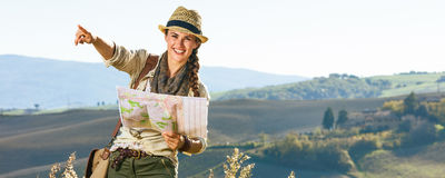 Happy woman hiker on Tuscany hike holding map and pointing Stock Image