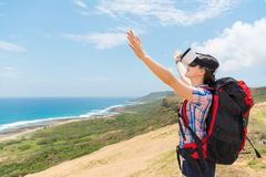 Happy woman hiker wearing a virtual reality device. Through 3D images enjoy the immediate coastal scenery and raised her hands experience the sea breeze with Royalty Free Stock Photos