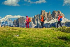 Happy woman hikers with backpacks walking in mountains, Dolomites, Italy stock photography