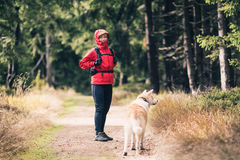 Happy woman hiking with dog in woods Royalty Free Stock Photos