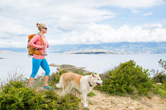 Happy woman hiking walking with dog on seaside trail Stock Photo