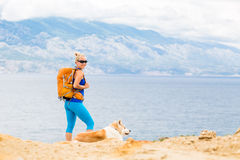 Happy woman hiking walking with dog on seaside trail Royalty Free Stock Image