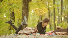 Happy woman hipster listen music on smart phone on autumn background. Woman model in park. Young female having fun over stock video