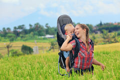 Happy woman hold child in backpack baby carrier royalty free stock photography