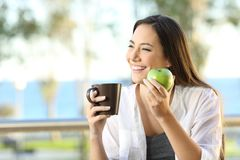 Happy woman holding an apple and a coffee mug. In an apartment balcony Royalty Free Stock Images