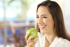 Happy woman holding an apple looking away. In the living room at home Stock Photos