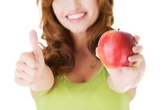 Happy woman holding an apple with thumb up Stock Images