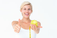 Happy woman holding an apple with thumbs up Stock Photography
