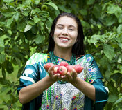 Happy woman holding apples, against green of summer park. Royalty Free Stock Images