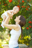 Happy woman holding in arm a baby in a garden Stock Photography