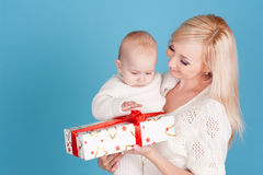 Happy woman holding baby boy with christmas present Royalty Free Stock Image