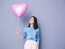 Happy woman holding balloon over gray background Stock Image