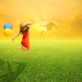 Happy woman holding balloons and jumping on grass field and suns. Et.holiday vacation concept Stock Image