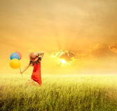 Happy woman holding balloons and jumping on grass field and suns. Et.holiday vacation concept Stock Photos