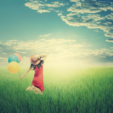 Happy woman holding balloons in yellow rice field and cloud sky. Summer holiday concept.Vintage Tone Royalty Free Stock Photo