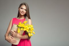 Young happy woman holding basket with yellow tulips. Gray backgr Stock Photos