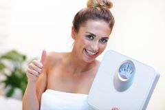 Happy woman holding bathroom scales in bathroom stock image