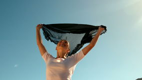 Happy woman holding black scarf above head on sunny day stock footage