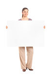 Happy woman holding a blank billboard. Full length portrait of a happy woman holding a blank billboard  on white background Royalty Free Stock Photography