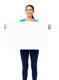 Happy Woman Holding Blank Billboard Over White Background. Portrait of happy woman holding blank billboard over white background. Vertical shot Stock Photos