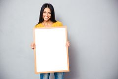 Happy woman holding blank board. Happy young woman holding blank board over gray background and looking at camera Stock Photo