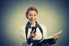 Happy woman holding book looking at phone seeing good news Royalty Free Stock Photo
