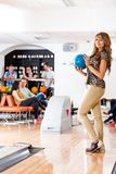 Happy Woman Holding Bowling Ball in Club Stock Photo