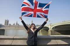Happy woman holding British flag while standing against Big Ben at London, England, UK royalty free stock photos