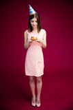 Happy woman holding cake with candles. Full length portrait of a happy woman holding cake with candles over pink background. Wearing in dress Royalty Free Stock Photos