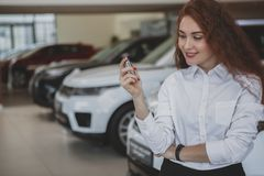 Happy woman holding car keys to her new automobile royalty free stock images