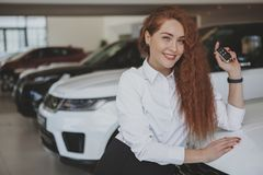 Happy woman holding car keys to her new automobile stock photo