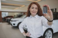 Happy woman holding car keys to her new automobile stock photography