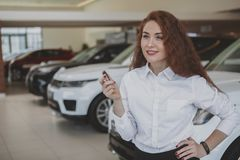 Happy woman holding car keys to her new automobile stock photos