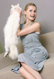 Happy woman holding cat while sitting in couch royalty free stock photos