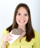 Happy woman holding chocolate bar against white background Royalty Free Stock Image