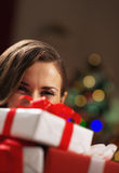 Happy woman holding christmas present boxes in front of face Royalty Free Stock Image