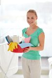 Happy woman holding cleaning stuff at home Stock Images